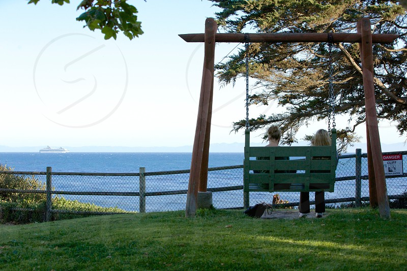 green painted swing bench with 2 woman sitting photo