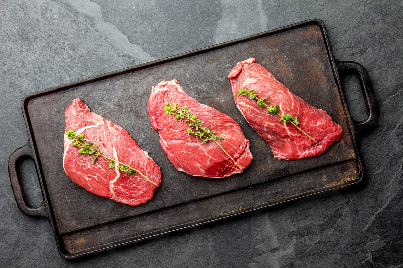 Raw beef steaks with herbs and spices on cast iron frying board top view. photo
