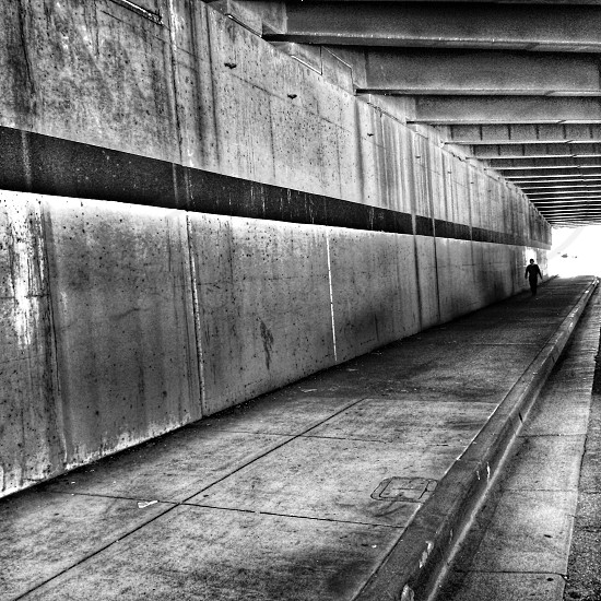 grayscale photography of human inside gray concrete enclosed passage photo