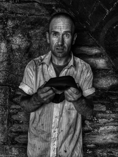 black and white photo of man holding hat photo