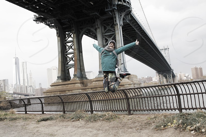 man in green sweatshirt jumping up with arms outstretched underneath overpass photo