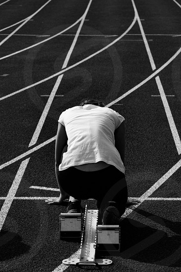 Woman at the starting line on the running track. photo