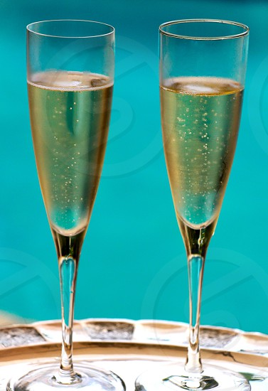 2 clear champagne glasses with brown liquid inside photo
