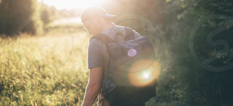 man in black cap with black backpack walking on grasses with sun rays photo