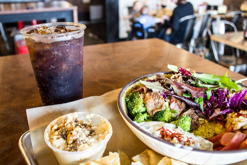 broccoli and lettuce in plate beside soda beverage in plastic cup on table photo