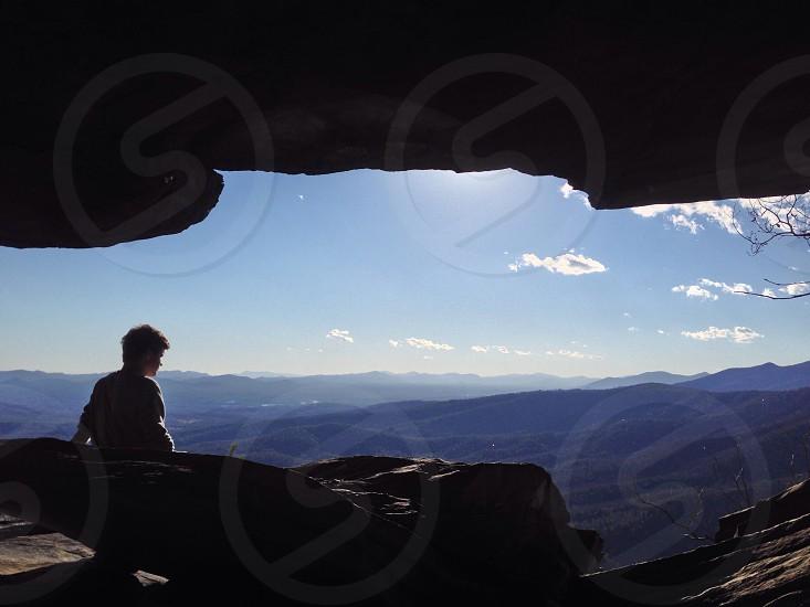 man sitting on rock view  photo