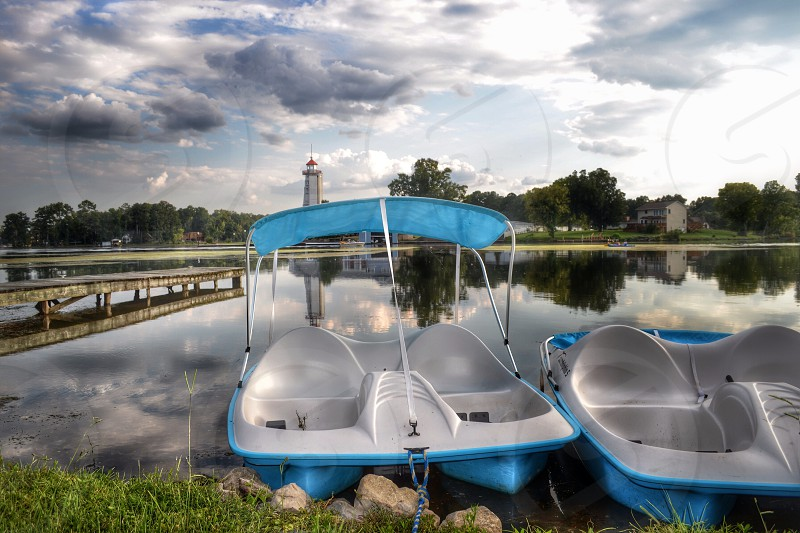 two blue-and-white pedal boats on body of water under white cloudy sky photo