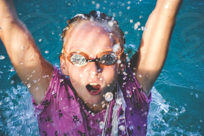 blur motion splash of water young girl wearing swimming goggles swimming backstroke photo