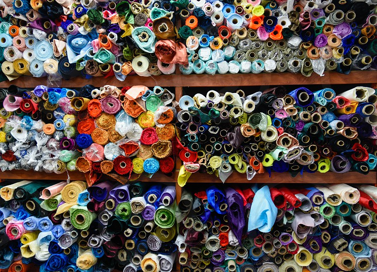 multicolored bolts of textiles in shelf photo