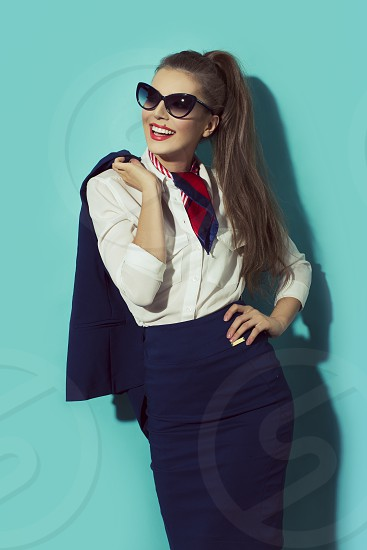 woman with blond hair wearing stewardess uniform with black butterfly sunglasses photo