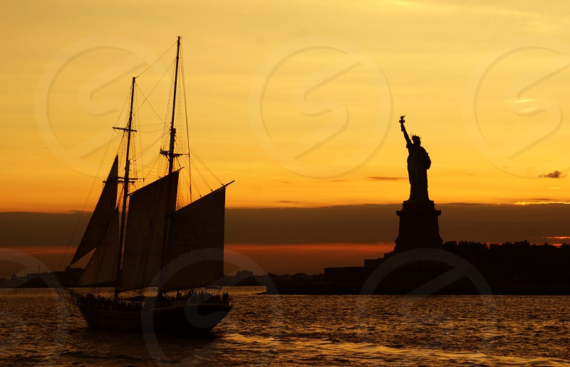 statue of liberty and sailing boat during dawn photo