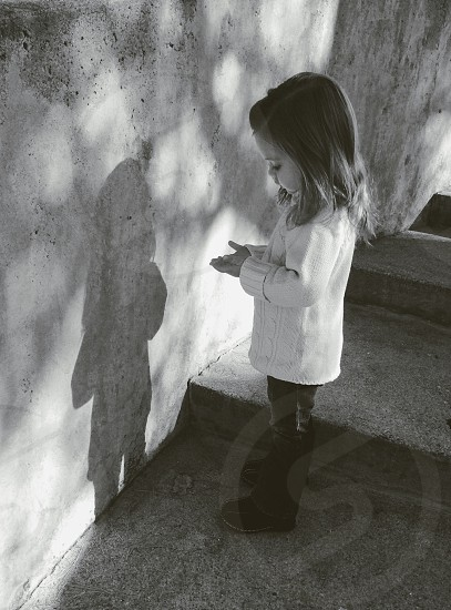 girl in white sweater near wall photo