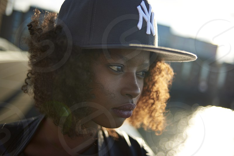 Close up of a beautiful young black woman wearing headphones in the city in an urban landscape during sunrise photo