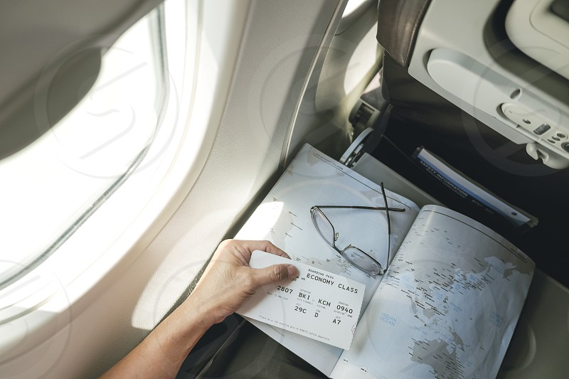 Top view of passenger holding boarding pass with map in his seat on board an airplane photo