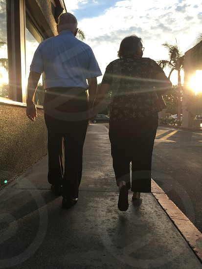senior couple still holding hands after 57 years married.  What an inspiration! photo