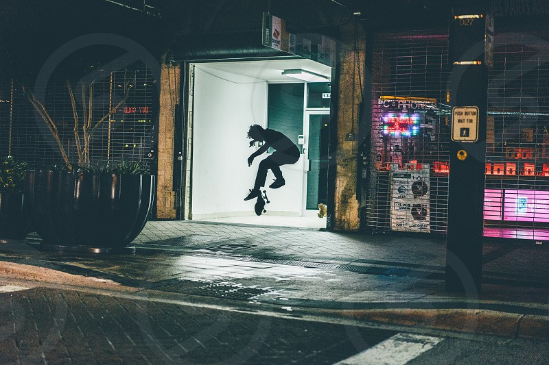 boy skateboarding during nightime photo