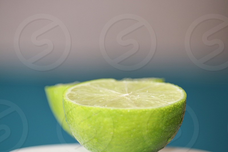 Juicy green ripe lime halved one half close up against soft turquoise aqua blurred background in studio photo