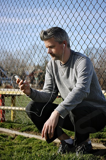 man using apple ear buds sitting beside metal fence photo