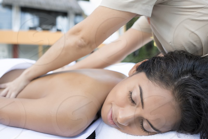 Close up of hispanic woman receiving a massage outdoors. photo