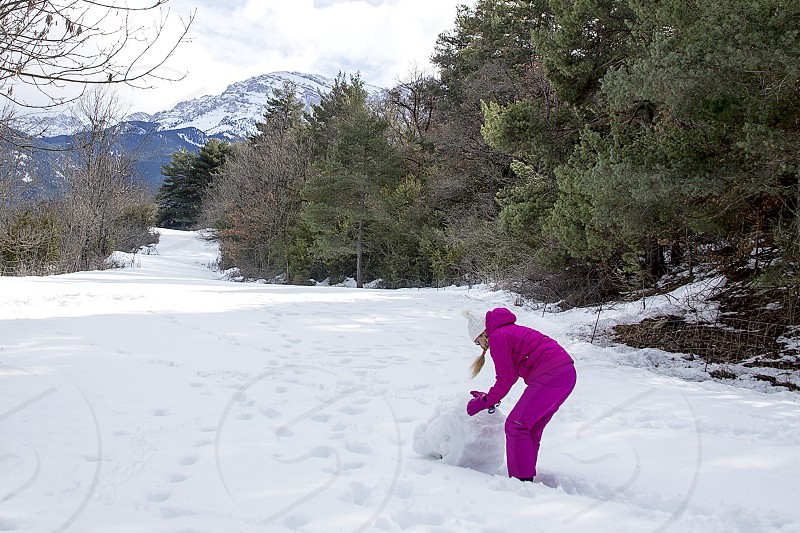 Young woman make a snowman on a sunny day in the winter snow-covered forest in the mountains. photo