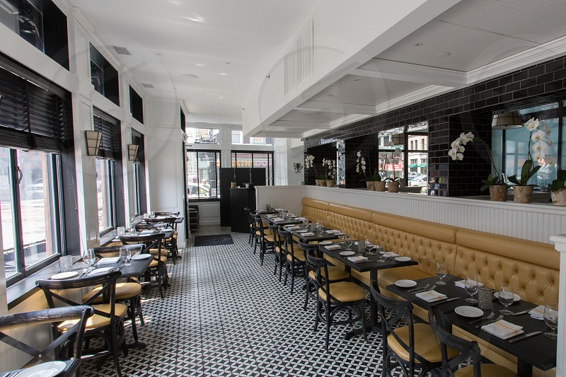 black tables and chairs under white roof inside restaurant photo