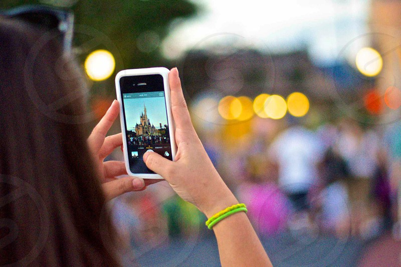 woman with dark hair holding up white phone to take a picture of castle photo
