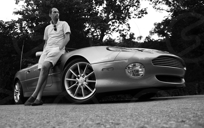 person leaning on aston martin photo