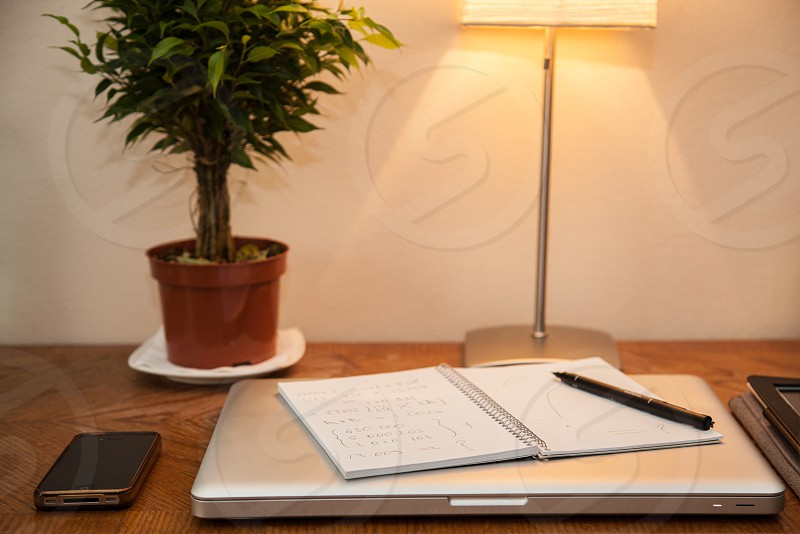 silver laptop with white spiral notebook and black pen on top photo