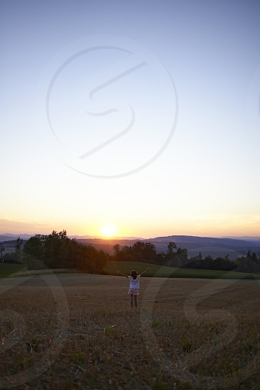 Young girl in a white dress standing in a field on a hill raising her arms towards the sunset photo