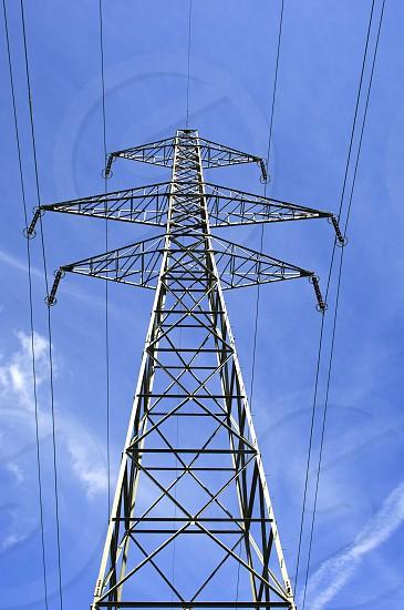 Electricity pylon against blue sky photo