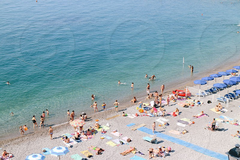 high angle view photography of group of people standing and lying on seashore near blue ocean during daytime photo