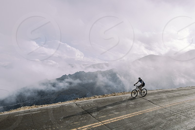 man riding on bicycle near sea of clouds photo