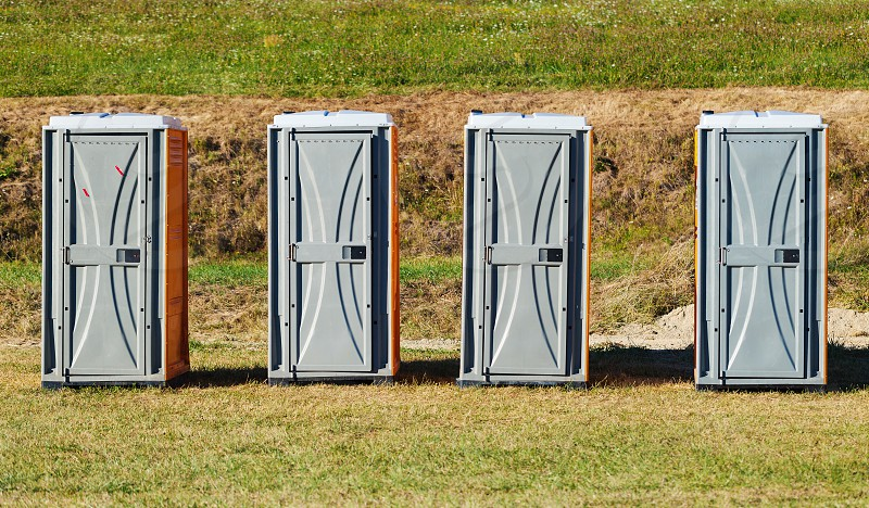 Four toilets on green field during sunny day.  photo