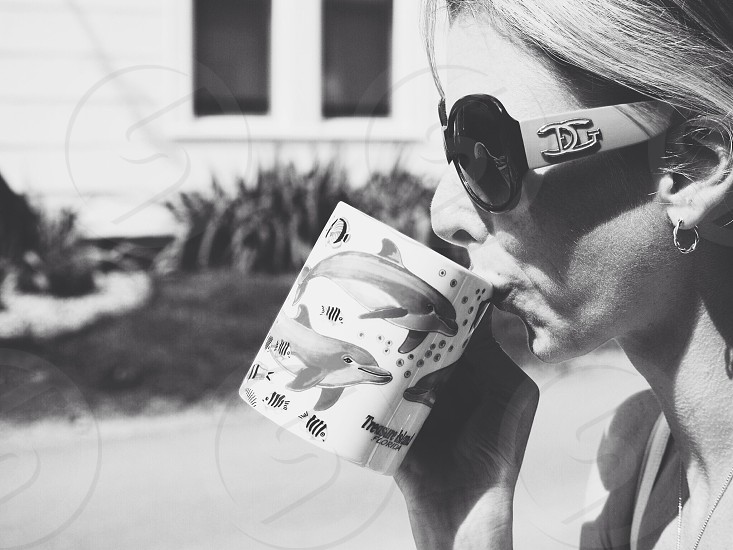 woman wearing dolce and gabbana sunglasses drinking from dolphin mug in greyscale image photo