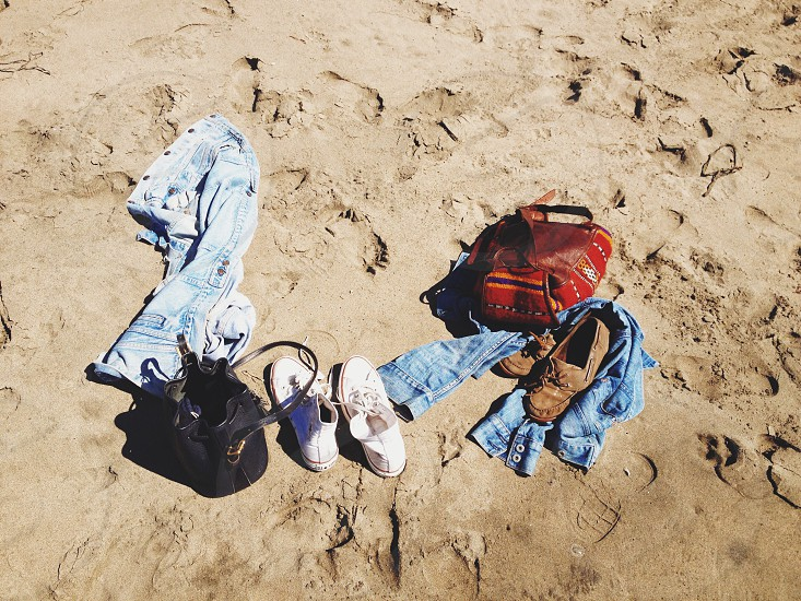 green denim jeans white sneakers black handbag and red handbag and brown boat shoes on sand photo