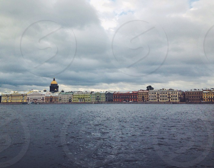 assorted-color concrete buildings near body of water under white sky during daytime photo