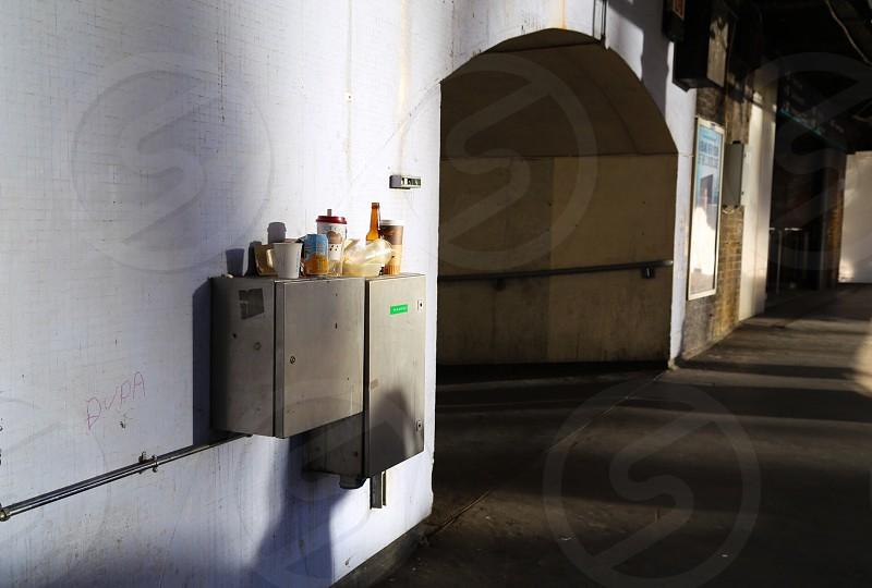 Trash path underground wall paper bottle urban suburb  London  England shadows  photo