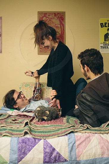2 women and man on bed photo