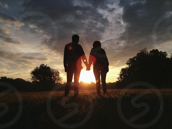 couple standing in sunset view silhouette  photo