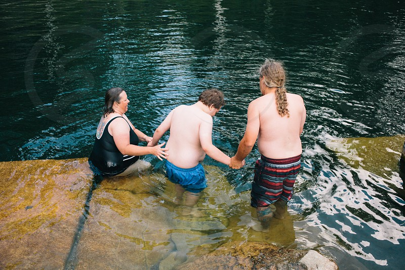woman and man on either side of brunet boy stepping into water photo