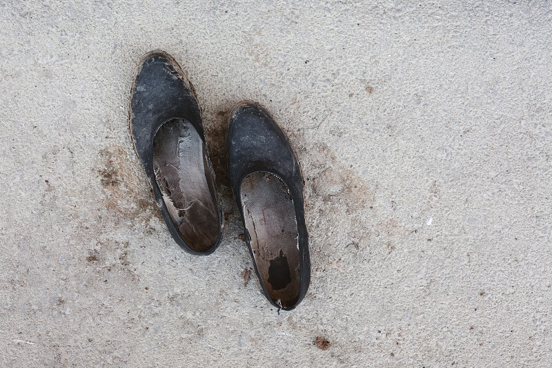 Closeup view of an old and dirty rubber shoes on asphalt abstract composition.  photo