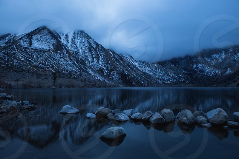gray rocky mountain across the lake under dark cloudy sky photo