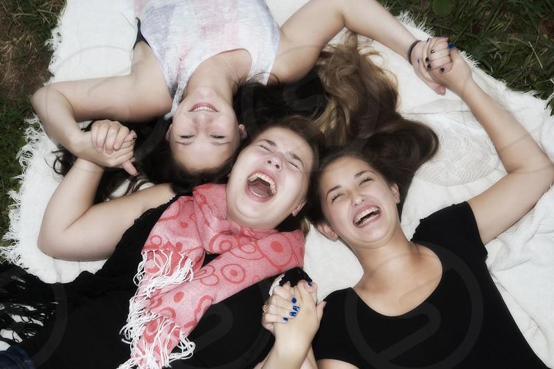 teenage girls laughing laying down photo