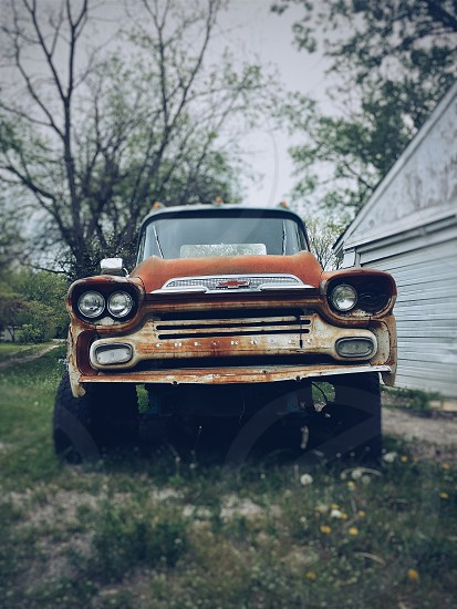 photo of a chevrolet brown classic car  near a white shed photo
