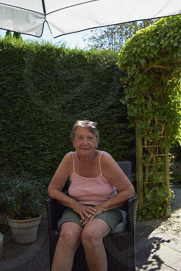 Portrait of an affluent elderly woman sitting in her back garden enjoying the summer sunshine photo