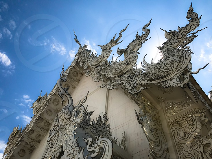 Outdoor day landscape horizontal colour Wat Rong Khun The White Temple Chiang Rai Thailand Thai Kingdom of Thailand travel tourism tourist wanderlust summer summertime temple Buddhist Buddhism spiritual pure holy carved ornate elaborate art modern sculpture sculpted east eastern hands silver mirror mosaic magical mythical blue sky building temple architecture Orient photo