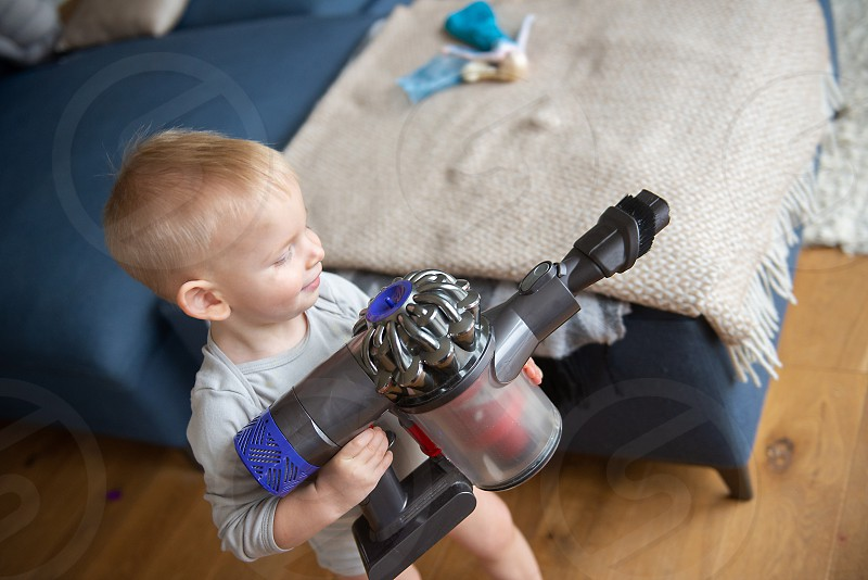 Blond baby boy is playing with a vacuum cleaner. photo