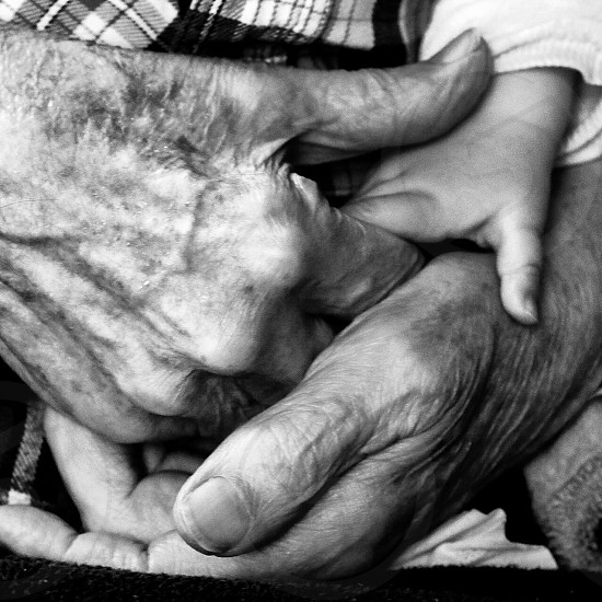 man holding child's hand greyscale photo photo