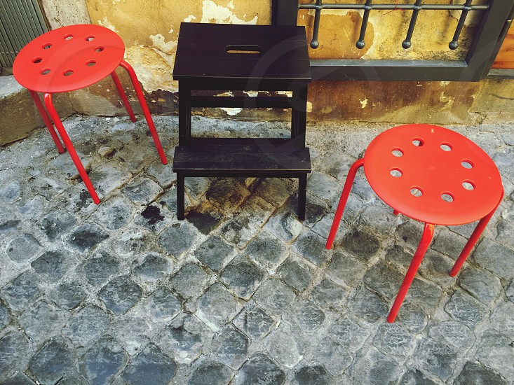 Stools on a cobblestone street photo