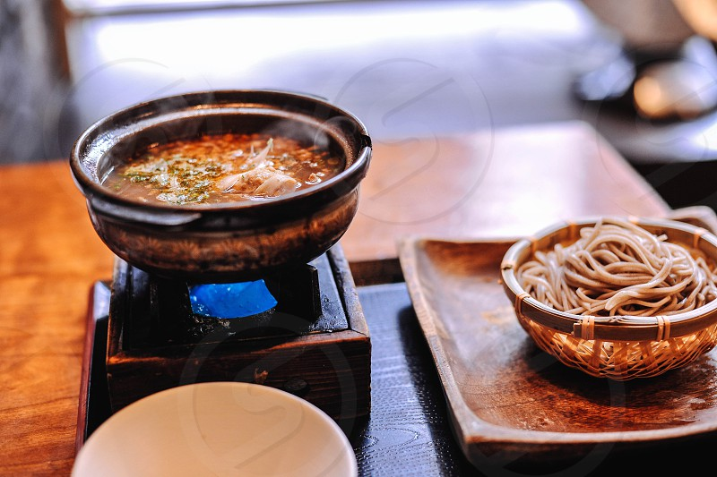 steaming bowl of soup on a tray with a bowl of noodles on a square wood plate photo